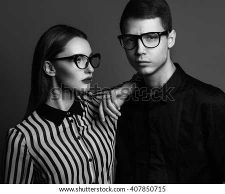 Eyewear concept. Portrait of gorgeous fashion couple in black clothes wearing trendy glasses and posing over gray background together. Perfect skin. Vogue style. Close up. Studio shot - stock photo