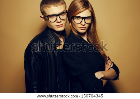 Eyewear concept. Portrait of gorgeous red-haired fashion twins in black clothes wearing trendy glasses and posing over beige background together. Perfect hair & skin. Natural make-up. Studio shot - stock photo