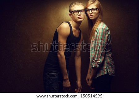 Eyewear concept. Portrait of gorgeous red-haired (ginger) fashion twins in casual shirts wearing trendy glasses and posing over golden background together. Hipster style. Copy-space. Studio shot - stock photo
