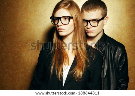 Eyewear concept. Portrait of gorgeous red-haired twins in black clothes wearing trendy glasses and posing over golden background together. Perfect hair & skin. Hipster style. Copy-space. Studio shot - stock photo
