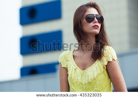 Eyewear concept. Portrait of gorgeous young woman in yellow-green handmade knitted top holding wearing aviator type sunglasses, posing in the street. Urban style. Copy-space. Close up. Outdoor shot