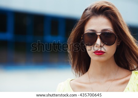 Eyewear concept. Portrait of gorgeous young woman in yellow-green handmade knitted top holding wearing aviator type sunglasses, posing in the street. Urban style. Copy-space. Close up. Outdoor shot - stock photo