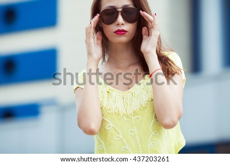 Eyewear concept. Portrait of gorgeous young woman in yellow-green handmade knitted top holding aviator type sunglasses, posing in the street. Urban style. Copy-space. Close up. Outdoor shot