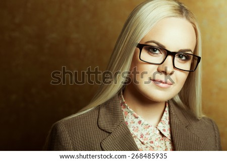 Eyewear concept. Portrait of young beautiful business woman wearing trendy glasses, casual shirt, jacket and posing over golden background. Copy-space. Close up. Studio shot