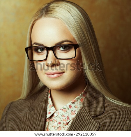 Eyewear concept. Portrait of young beautiful business woman wearing trendy glasses, casual shirt, jacket and posing over golden background. Close up. Studio shot - stock photo