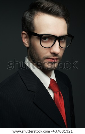 Eyewear concept. Portrait of young handsome man in black suit with trendy red tie, stylish glasses and looking at camera. Geek style. Close up. Studio shot