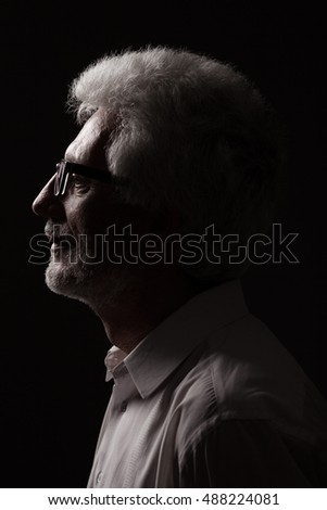 Eyewear concept. Profile portrait of 60-year-old man standing over black background. Close up. Classic style. Studio shot