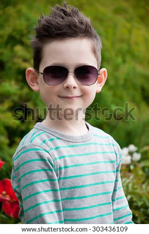 Eyewear concept. Stylish baby boy with dark hair in trendy sunglasses  and in a striped polo-neck, the  standing, in the park with green grass. Hipster style. Sunny weather. Close up. Outdoor shot - stock photo