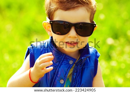Eyewear concept. Stylish baby boy with ginger (red) hair in trendy sunglasses and blue jacket standing in the park with green grass. Hipster style. Sunny weather. Close up. Outdoor shot
