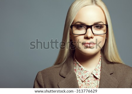 Eyewear fashion concept. Portrait of young beautiful blonde girl wearing trendy glasses, casual shirt, jacket and posing over gray background. Close up. Copy-space. Studio shot - stock photo