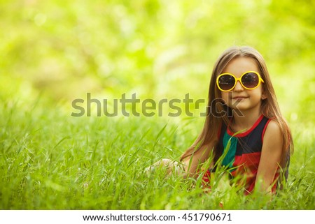 Eyewear, shopping & discount concept. Portrait of funny and sweet little girl wearing fashionable dress with avantgarde motives. Long brown hair in the wind. Close up. Copy-space - stock photo