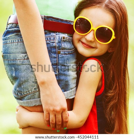 Eyewear, shopping & discount concept. Portrait of funny and sweet little girl wearing fashionable dress with and hugging mother in jeans shorts. Close up. Copy-space. Outdoor shot