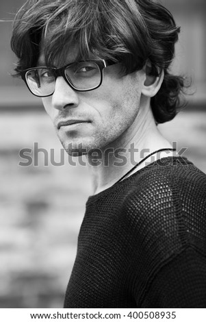 Eyewear, street fashion concept. Portrait of romantic charismatic man wearing stylish eyeglasses. Close up. Monochrome, black and white outdoor shot.