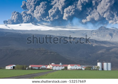 Eyjafjallajokull in Iceland erupting, ash plume against blue sky above the farm Thorvaldseyri, green fields in the foreground - stock photo