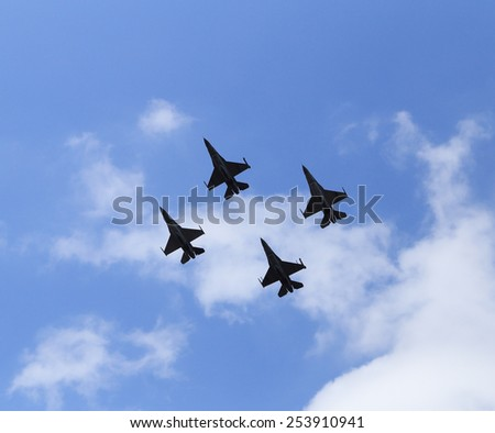 f16 falcon fighter jet flying on blue sky background - stock photo