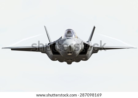 F35 front view close up flying to the camera with chem trails - stock photo