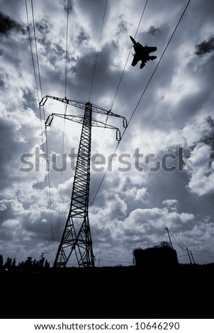 F15 high performance military fighter jet flying low over electricity pylon