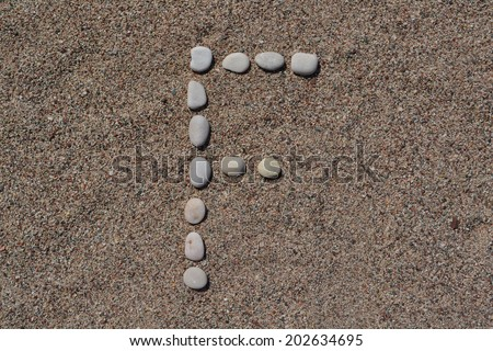 F letter made of stones on sand  - stock photo