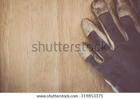 fabric and leather worn out work gloves on a wood background - vintage look processing - stock photo