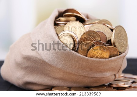 Fabric bag full of Ukrainian coins on wooden background - stock photo