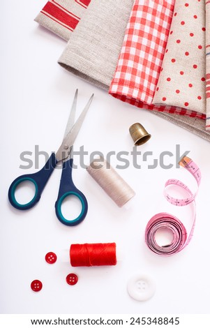 Fabric for decoration stacked and accessories for needlework. Tools for needlework thread scissors and tape measure on white background. - stock photo