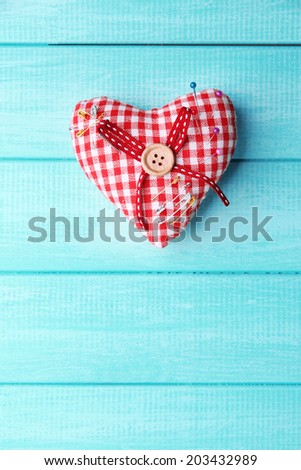 Fabric heart with color and safety pins on wooden background - stock photo