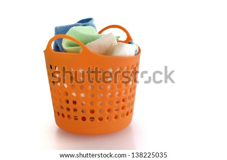 fabric in orange plastic basket isolated on white - stock photo
