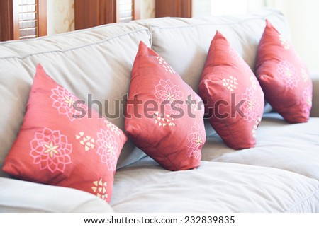 Fabric sofa with red decorative pillows natural - stock photo