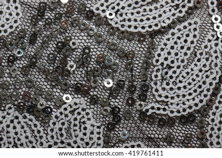 Fabric with bright sequins for background. Closeup of fabric embroidered with sequins. - stock photo