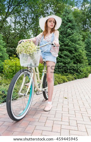 Fabulous attractive woman wearing a beautiful white hat sitting on her bicycle with a bouquet of little white flowers in a basket in a park with background of different trees - stock photo