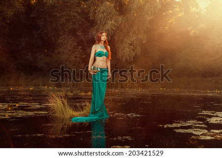 Fabulous girl of the river with a ship in the hands. - stock photo