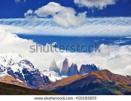 Fabulous harmony of the national park Torres del Paine in Chile. Three rocks Torres are surrounded by picturesque clouds  - stock photo