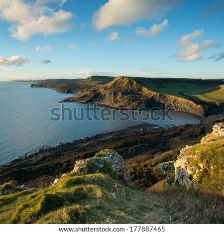 Fabulous late afternoon view across Chapman's Pool with the sun reflecting off the face of Houns-tout Cliff. Dorset, UK. Part of Dorset's Jurassic coastline.
