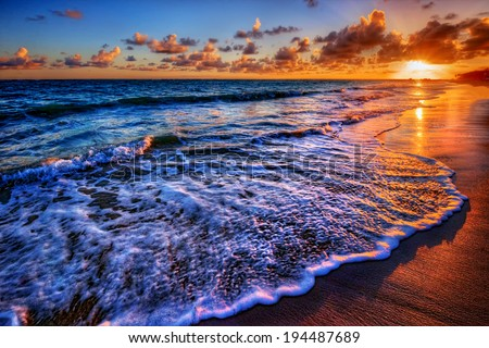 Fabulously shaped wave breaking on a sandy beach at sunrise - stock photo