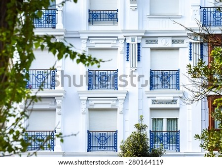 Facade detail with its white windows and blue railings - stock photo