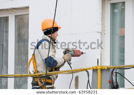 facade laborer in uniform and hard hat worker making a hole in wall with drill - stock photo