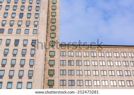 Facade of a big multi-storey building with several windows and blue sky in the background - stock photo