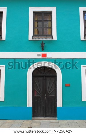 Facade of a blue painted house with dark door and windows - stock photo