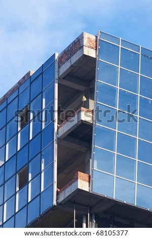facade of a building under construction with coated blue windows and sky - stock photo