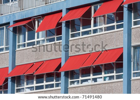 Facade of a modern building with red sunshades - stock photo