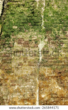 Facade of a moss infested grungy retention brickwall, for textural background.  - stock photo