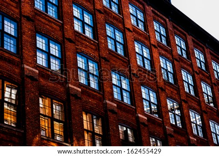 Facade of a redbrick city building with the sky reflected in the windows