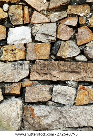 Facade of a rugged granite stone wall, for textural background. - stock photo