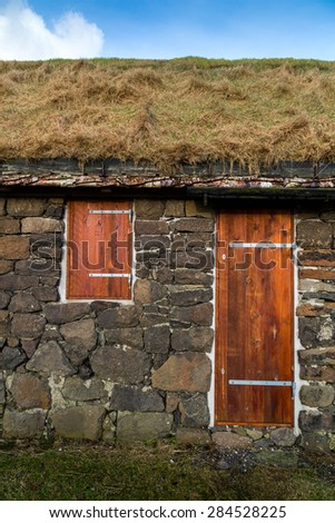 Facade of a typical rural building with natural grass roof and silver birch rafters in Torshavn, Faroe Islands - stock photo