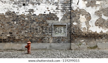 Facade of an ancient brick wall along a cobble stone street with an medieval ornate square window and a red fire hydrant. - stock photo