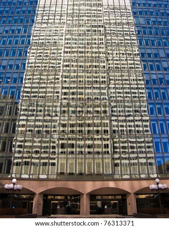 Facade of an office building with reflection of another building in the windows in Montreal - stock photo