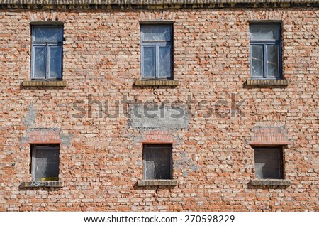 facade of an old abandoned building with decaying exterior and dirty windows - stock photo