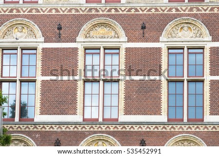 Facade of an old building, where you can see relives famous Dutch painters, in Amstardam.