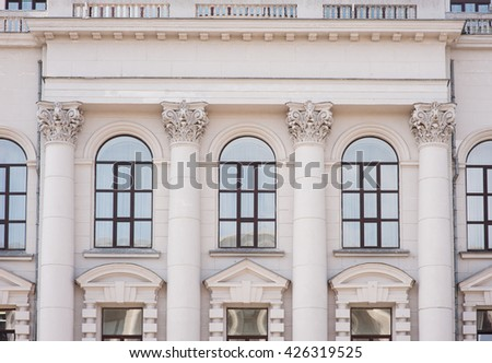 facade of an old building with columns and windows - stock photo