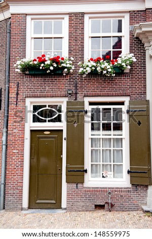 Facade of an old holland red brick house with white window frames